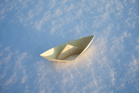 beige paper boat in the snow. Winter