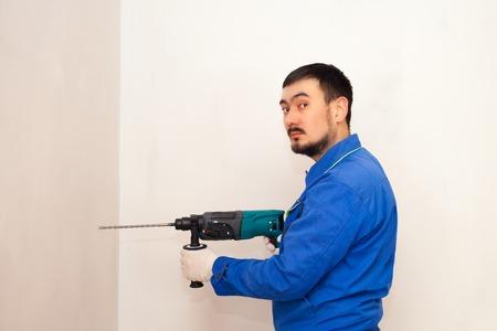 Taladro en las manos. trabajando el taladro de pared taladro de impacto, martillo