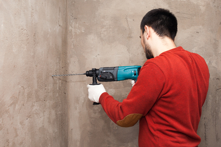 Drill in hands. working the wall drill impact drill, hammer
