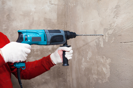 Drill in hands. working the wall drill impact drill, hammer Banque d'images
