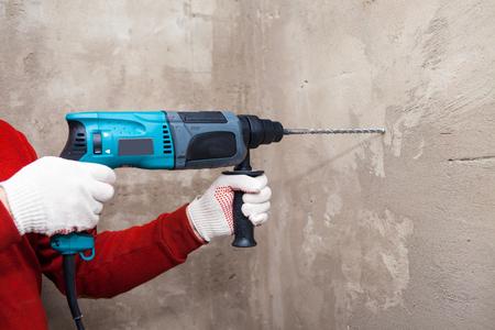 Taladro en las manos. trabajando el taladro de pared taladro de impacto, martillo Foto de archivo