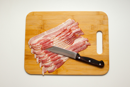 Sliced bacon with salad leaves on the wood background Archivio Fotografico