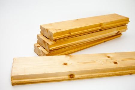 pila de tablas de pino para el dispositivo de piso. Tablero de piso sobre fondo blanco. Decking en taller como fondo. Crear fotofone
