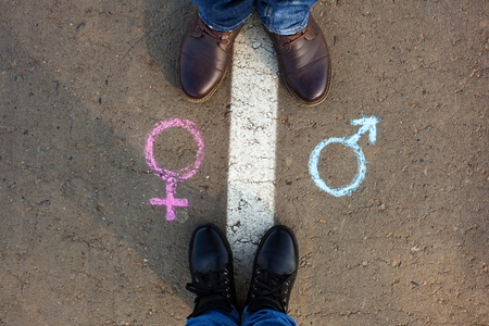 Gender symbols or signs for male and female drawn on asphalt. Male and female legs. The concept of gender equality.