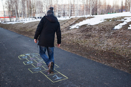 A young man playing hopscotch on asphalt. Good mood and spring in Russia. A bearded man recalls his childhood.Sunset Фото со стока - 122731435