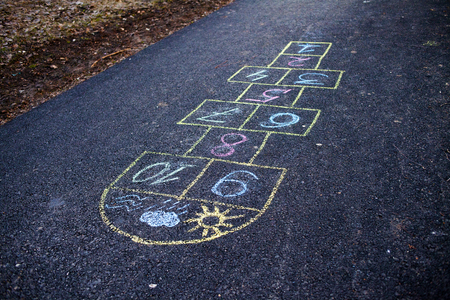 Hopscotch game being drawn with a chalk on the asphalt ground as seen from above. Childhood memories, joy and positive. Stockfoto