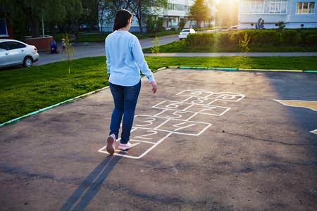Cute girl playing hopscotch