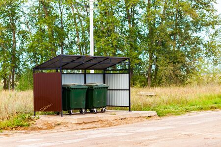 Two green dumpsters on the street under a canopy. Garbage reform in Russia. Container Stok Fotoğraf