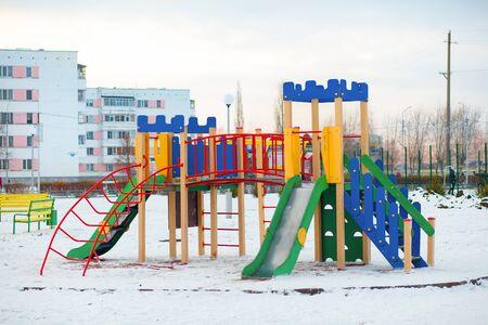 Un parque infantil, un tobogán situado en la arena. Día soleado de invierno