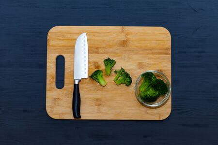 A woman cuts broccoli with a knife on a cutting Board.