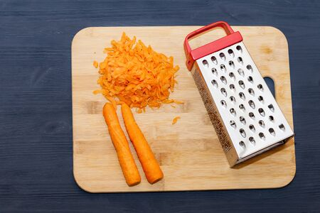 The composition of the grated carrots. grated carrots on a cutting Board. Black wooden background