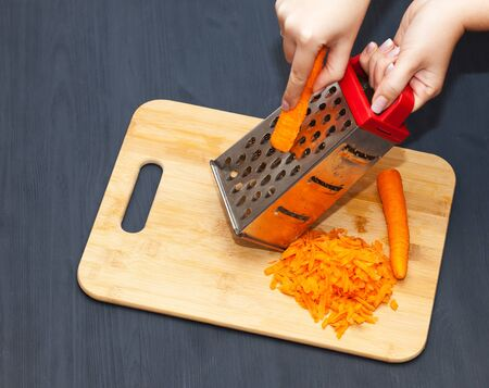 Female hands grating carrot on metal grater. Black wooden background Zdjęcie Seryjne