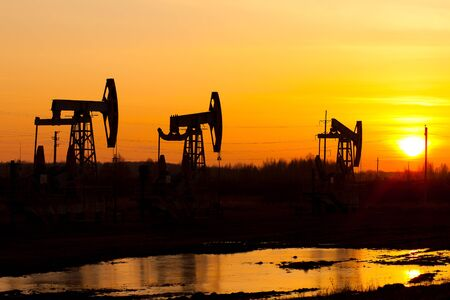 Working oil pump in rural place at sunset. Russia