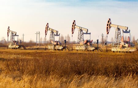Oil pump jack rocking with pipeline in the background. Rocking machines for power generation. Extraction of oil