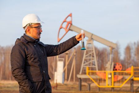 Engineer in a white helmet on an oil rig with a tablet. Oil production in Russia, Republic of Bashkortostan. Quality control