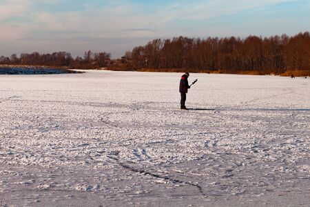 fisherman figure on little, natural, frozen winter river, makes ice hole with a hand ice auger, man's silhouette in warm clothes. RussianFisherman on ice. Life style.