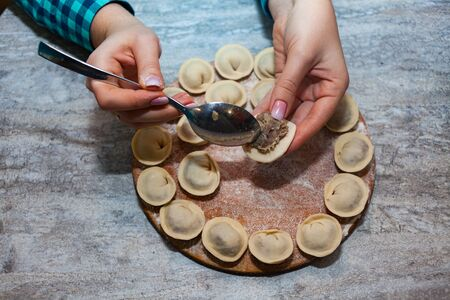 woman preparing dumplings hands. Sculpt pierogy and pelmeni concept. Include rustic cutting board, making pierogies on a rustic wooden table. Dumpling recipe.