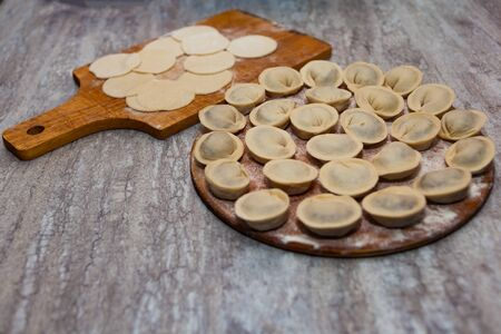 Sculpt pierogy and pelmeni concept. Include rustic cutting board, making pierogies on a rustic wooden table. Zdjęcie Seryjne