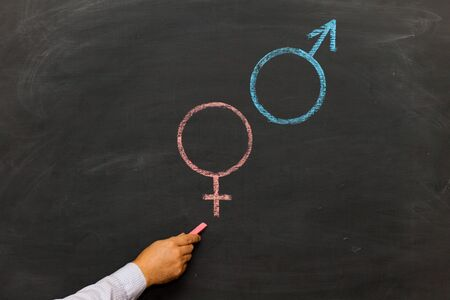 Gender symbols or signs for the male and female sex drawn on a blackboard. Sex Ed Stockfoto