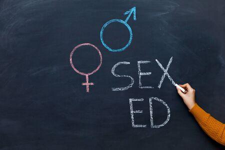School blackboard with text SEX ED. Female hand with chalk. Stockfoto