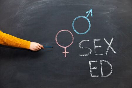 School blackboard with text SEX ED. Female hand with chalk. Imagens
