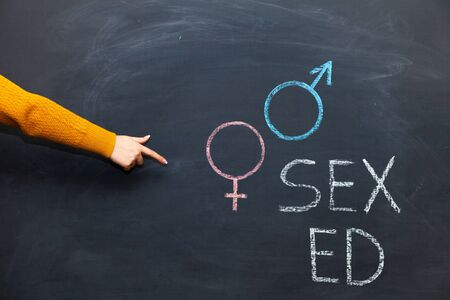 School blackboard with text SEX ED. A womans hand points