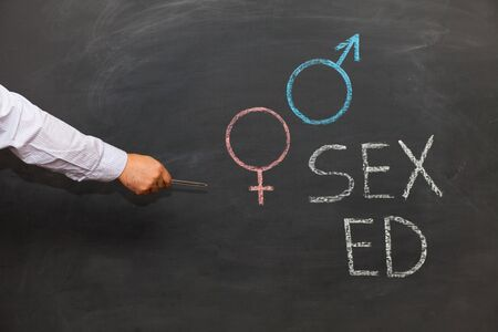 School blackboard with text SEX ED. Male hand pointing with pen