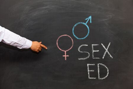 School blackboard with text SEX ED. Male hand pointing Stockfoto