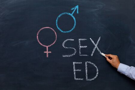 School blackboard with text SEX ED. Male hand with chalk.