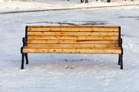A yellow color painted wooden bench with white beautiful snow and a basket in a park in winter in a sunny day.