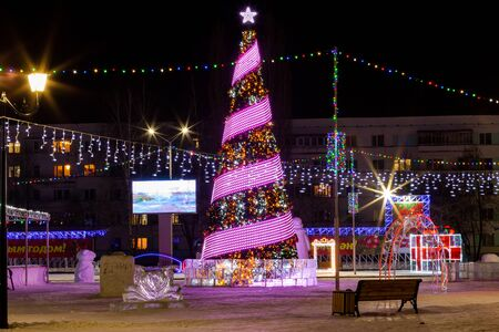 Bottom view on Christmas tree on the city square in the Republic of Bashkortostan. Decorated fir tree for New Year celebration. Agidel