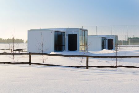 Beautiful houses in the winter recreation Park. Prefabricated houses made of sandwich panels. Frame construction. Russia