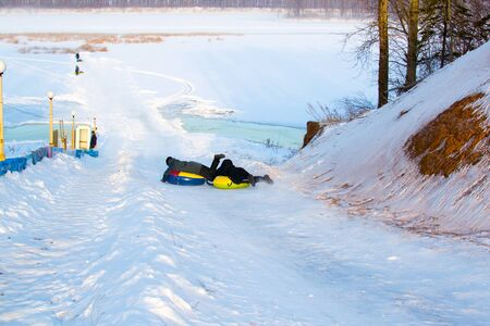 Company of friends ride down by snowing hill with snow tube
