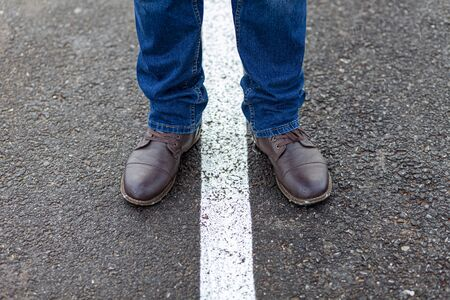Men's feet in brown shoes on middle of road roadmap road lines.