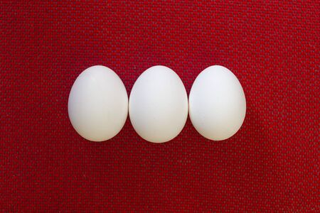 Three White egg on the red background in center. Red texture background