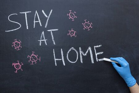 Stay at home text on the chalkboard. Hand in a medical glove with chalk. The concept of self-isolation