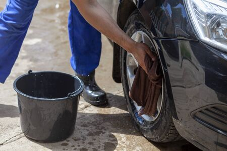 a man washes a car wheel with a rag