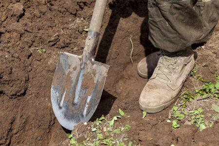 a man digs a hole with a shovel on a farm