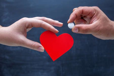 The hand holds out a white tablet in the symbol of the heart