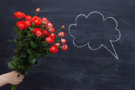 Bouquet of roses on a chalkboard background. A speech cloud drawn in chalk.