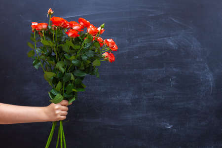 bouquet of roses in hand on a chalkboard background