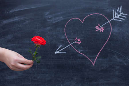 Rose on a chalkboard background, heart drawn in chalk