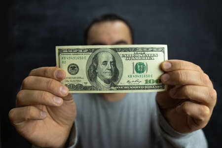 A man holds money, a hundred-dollar bill in the hands of a man in front of his face