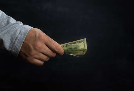 A man's hand holds out a hundred-dollar bill on a dark background