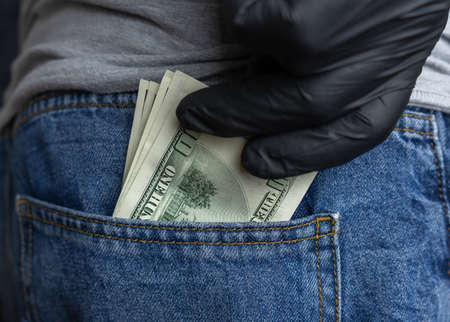 A hand in a black medical glove pulls hundred dollar bills from the back pocket of his blue jeans Stockfoto