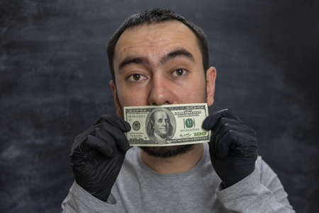 The bribe taker holds a hundred-dollar bill in front of his mouth.