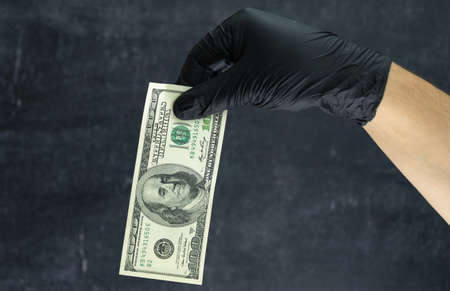 A hand in a black nitrile glove holds a hundred dollars against a dark background Stockfoto