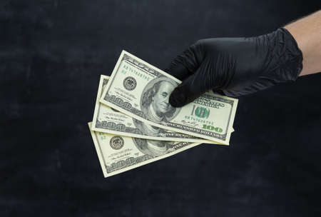 A man's hand in black medical gloves holds three hundred dollar bills in his hand