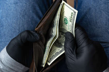 A man in black medical gloves counts the remaining money in his wallet. Hundred-dollar bills in your wallet