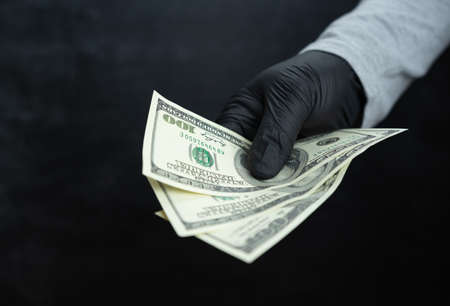 A black gloved hand holds three hundred dollars against a dark background